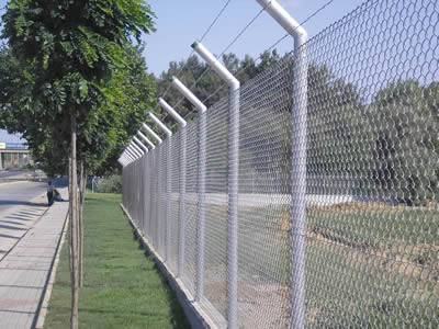 Chain link mesh with intermediate post is installed along the street.