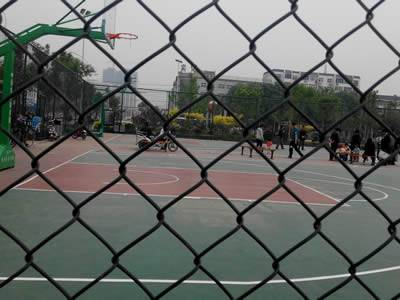 Black chain link mesh with square holes for basketball fencing, many people in it playing.