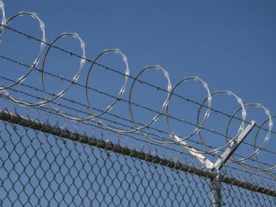 Concertina razor wires and barbed wires are installed at the top of chain link fence.