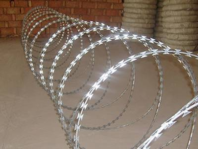 A roll of double spiral concertina razor wire on the ground.