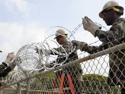 Three soldiers are installing the concertina razor wire onto chain link fence.