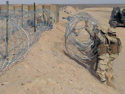 Several soldiers are installing the concertina razor wire in the military site.