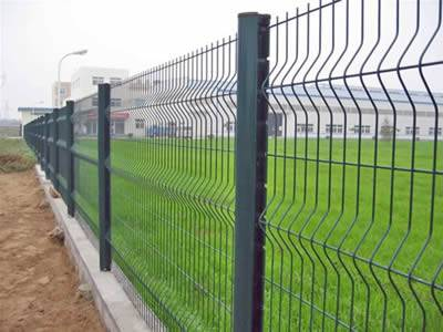 Several pieces of green PVC coated curvy welded wire mesh fence are installed in the factory.