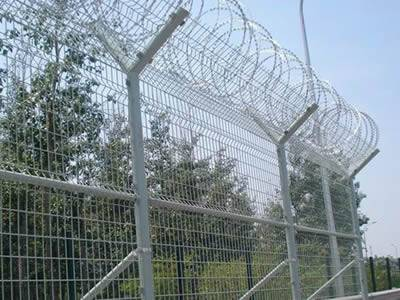 Several pieces of galvanized curvy welded wire mesh fences with razor wires on the top of the fence.