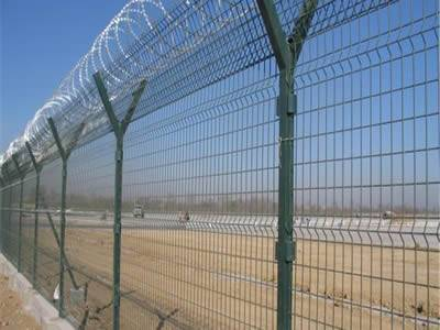 Several pieces of PVC coated curvy welded wire mesh fences with razor wires on the top of the fence.