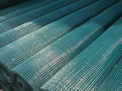 Dark-green PVC coated welded wire mesh rolls lying on the ground