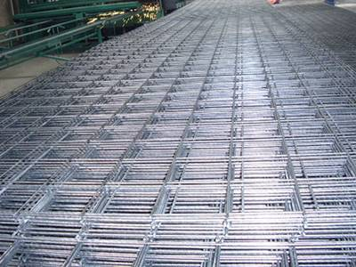 Galvanized welded wire panels on the ground in workshop beside a welded wire mesh machine
