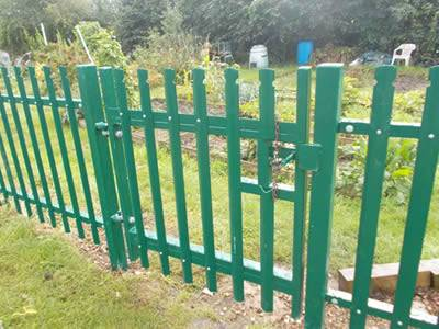 Green color palisade fence and gate are surrounding the garden.