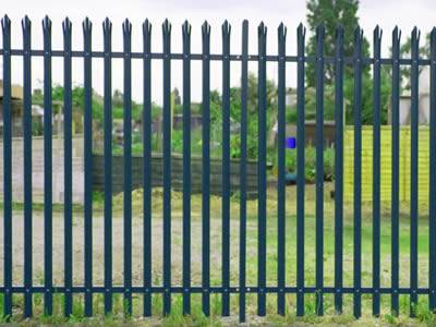 Dark green palisade fence is surrounding the factory.