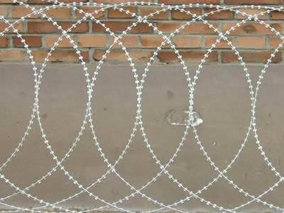 A piece of flat warp type razor wire is lying on the wall.