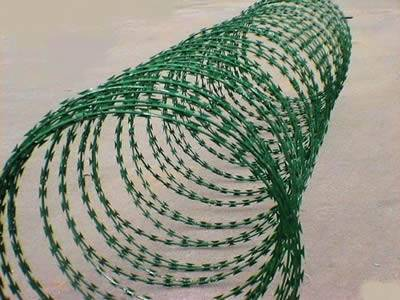 A roll of green PVC coated concertina razor wire on the ground.