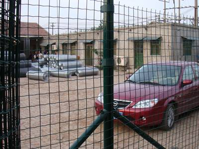Green PVC coated welded euro fence, a red car and many rolls of wire mesh in the yard