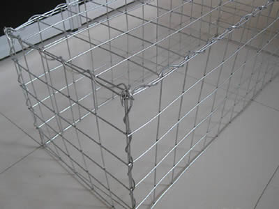 A welded gabion on the ground and connected by the lacing wire.