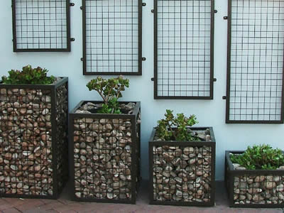 Four welded gabion with different height on the ground with plants in the pot.