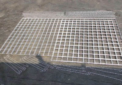 Welded gabion panels, spiral wires and stiffeners are on the ground.
