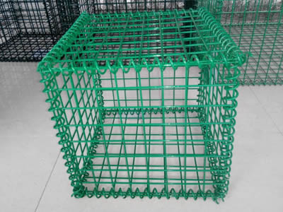 A green color PVC coating welded gabion on the ground.