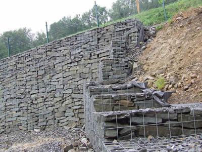 Several layers of welded gabions are piled up on the slope.