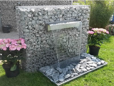 A welded gabion waterfall in the garden with two pot of flowers on the side.