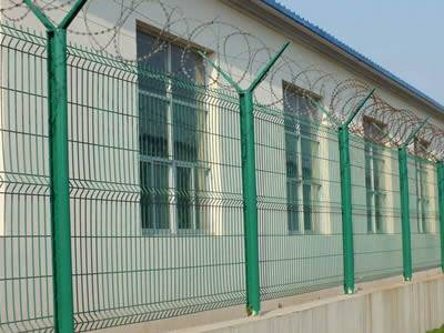 Several welded razor wire are installed along the factory wall.