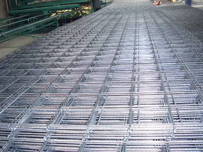 A stack of galvanized welded reinforcing concrete meshes on the ground.