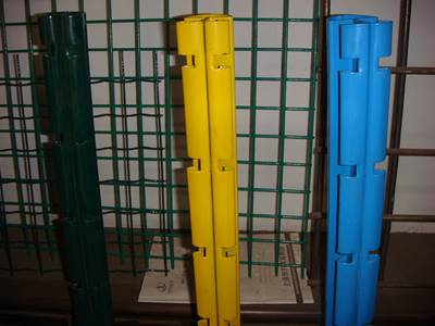 Green welded wire panels and three PVC coated fence post in green, yellow, and blue color