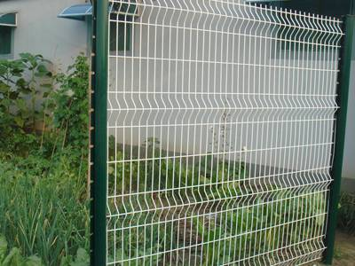 A Piece Of White Welded Wire Panel Installed With Green Posts